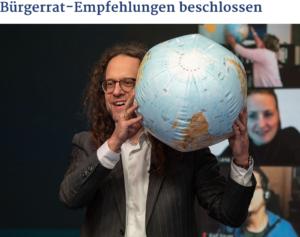 Screenshot: Mann mit Globus (Ball). Im Hintergrund Bilder von Videokonferenzen