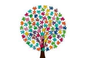 Stilisierter Baum mit bunten Blättern in Form von Puzzleteilen