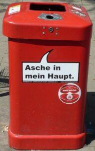 """Roter Abfalleimer - Standort: Hamburg. Beschriftung: """"Asche auf mein Haupt."""""""