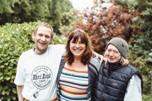 Drei Personen Arm in Arm: DRAUSSENSEITER-Chefredakteurin Christina Bacher mit Adam und Gabi vor der OASE